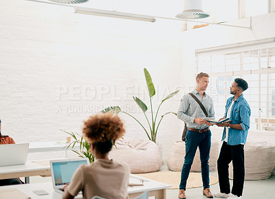 Buy stock photo Cropped shot of two handsome young businessmen standing together and having a discussion in a coworking office space