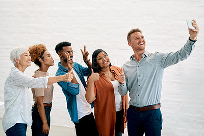 Buy stock photo Cropped shot of a handsome young man standing and using his cellphone to take a selfie with his coworkers
