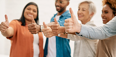 Buy stock photo Cropped shot of a diverse group of businesspeople standing together and showing a thumbs up in the office
