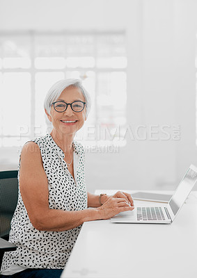 Buy stock photo Portrait of a senior businesswoman using a laptop in a modern office