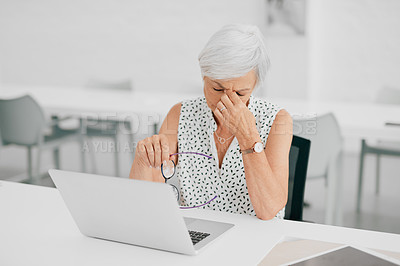 Buy stock photo Shot of a senior businesswoman looking stressed while using a laptop in a modern office