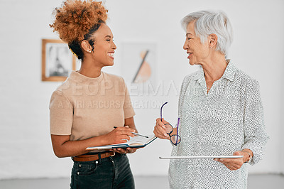 Buy stock photo Shot of two businesswomen having a discussion in a modern office