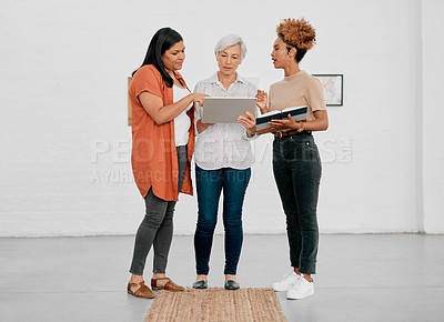 Buy stock photo Shot of a group of businesswomen using a digital tablet in a modern office