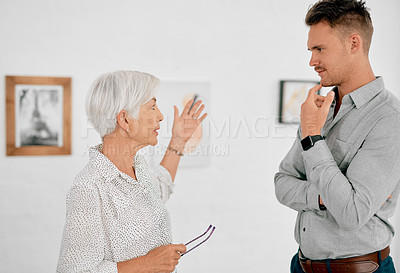 Buy stock photo Shot of a senior businesswoman having a discussion with a young businessman in a modern office