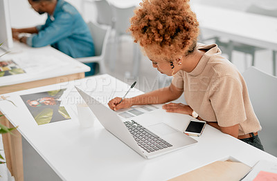 Buy stock photo Shot of a young businesswoman writing in a notebook in a modern office