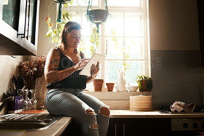 Buy stock photo Shot of a young woman using a digital tablet in the kitchen at home