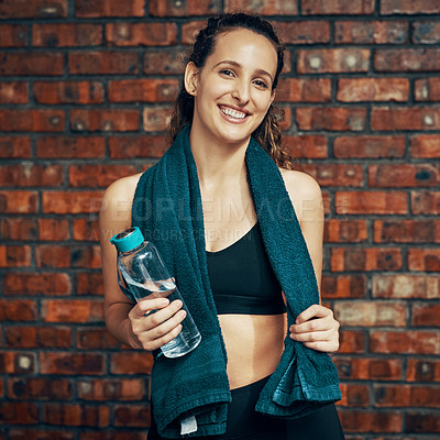 Buy stock photo Cropped shot of a young woman posing with a water bottle and her towel at the gym