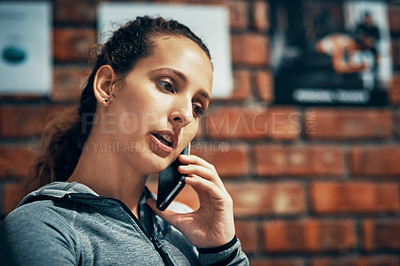 Buy stock photo Cropped shot of a fitness instructor talking on her cellphone