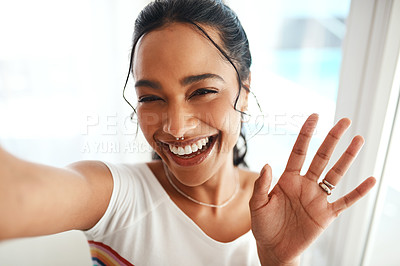 Buy stock photo Cropped portrait of an attractive young blogger standing in her home and waving at the camera during a selfie
