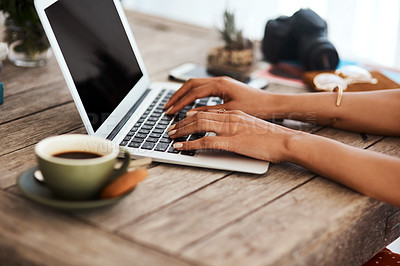Buy stock photo Cropped shot of an unrecognizable businesswoman sitting alone in her home office and using her laptop