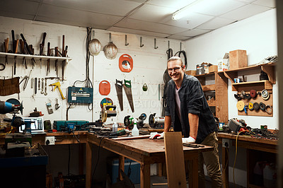 Buy stock photo Portrait of a cheerful young male carpenter taking a quick break while working inside of his workshop at home during the night