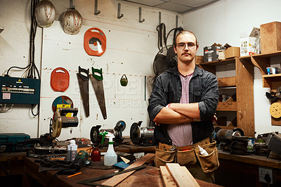 Buy stock photo Portrait of a confident young male carpenter standing with his arms folded inside of his workshop at night