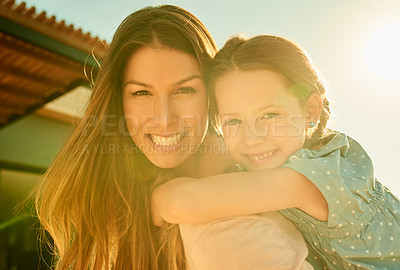 Buy stock photo Cropped shot of a woman carrying her daughter on her back