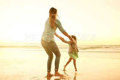Buy stock photo Shot of a woman and her young daughter enjoying themselves on the beach