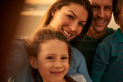 Buy stock photo POV shot of a happy family taking selfies on the beach