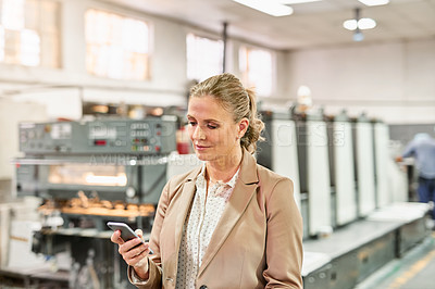 Buy stock photo Shot of a mature woman using a smartphone while working in a factory