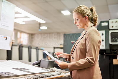Buy stock photo Shot of a mature woman going through paperwork while working in a factory