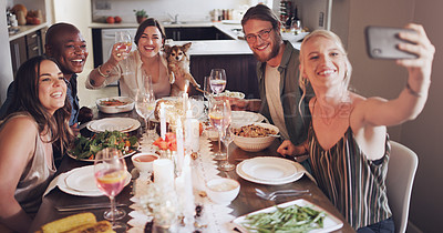 Buy stock photo Shot of a group of young friends taking selfies during a dinner party at home