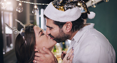 Buy stock photo Shot of a happy young couple kissing during a Christmas party with friends at home