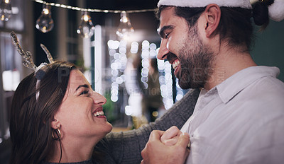 Buy stock photo Shot of a happy young couple dancing during a Christmas party with friends at home