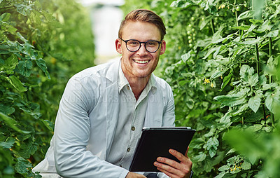 Buy stock photo Portrait of a handsome young scientist using a digital tablet while studying plants and crops outdoors on a farm