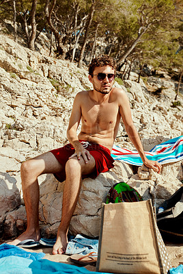 Buy stock photo Full length shot of a handsome young man sitting on rocks while relaxing outdoors by a lake in Spain