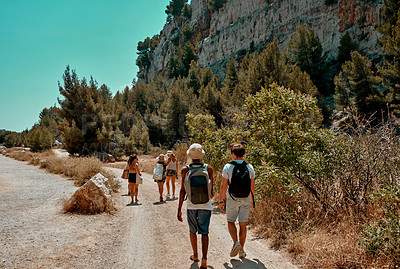 Buy stock photo Rearview shot of a group of friends walking on a dirt road while vacationing together outdoors in Spain
