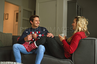 Buy stock photo Shot of a young couple enjoying a coffee break at Christmas time on the sofa at home