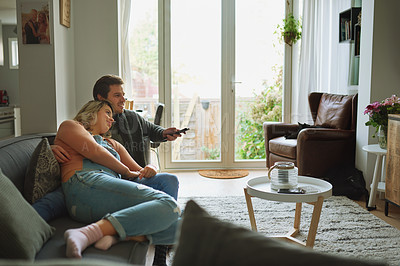Buy stock photo Shot of a young couple watching tv together on the sofa at home