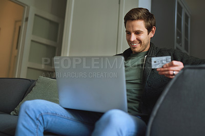 Buy stock photo Shot of a young man using a credit card and laptop on the sofa at home