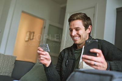 Buy stock photo Shot of a young man using a credit card and smartphone on the sofa at home