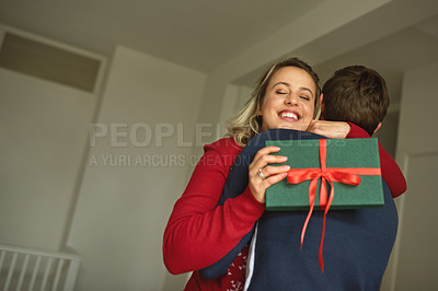 Buy stock photo Shot of a young couple changing Christmas gifts at home