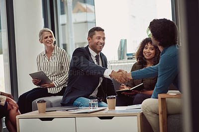 Buy stock photo Shot of two businesspeople shaking hands during a meeting in an office