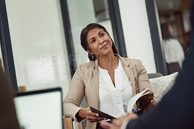 Buy stock photo Shot of a mature businesswoman having a discussion with a colleague in an office