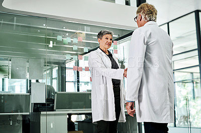 Buy stock photo Cropped shot of two mature doctors shaking hands while standing in a hospital