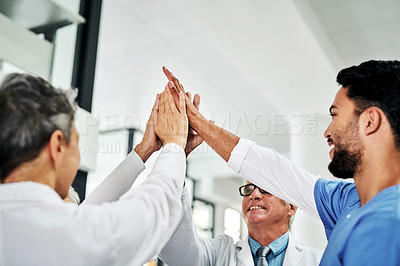 Buy stock photo Cropped shot of a diverse group of medical practitioners joining their hands together in unity in a hospital