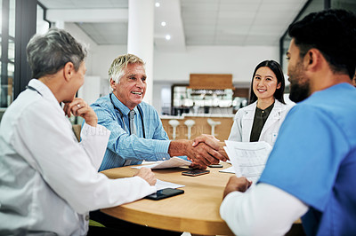 Buy stock photo Cropped shot of two medical practitioners shaking hands during a meeting in a hospital