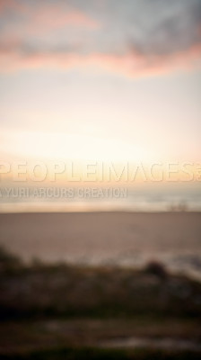 Buy stock photo Defocused shot of a beach at sunset