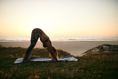 Buy stock photo Full length shot of an unrecognizable woman holding a downward facing dog position during a yoga session outdoors