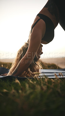 Buy stock photo Cropped shot of an attractive young woman holding a downward facing dog position during a yoga session outdoors