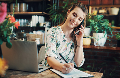 Buy stock photo Cropped shot of an attractive young businesswoman sitting alone in her floristry and making notes while on a phonecall