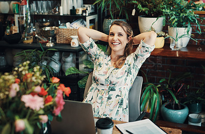 Buy stock photo Cropped portrait of an attractive young businesswoman sitting with her hands behind her head and feeling accomplished in her floristry