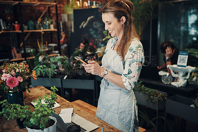 Buy stock photo Cropped shot of an attractive young businesswoman standing in her floristry and using her cellphone to photograph her flowers