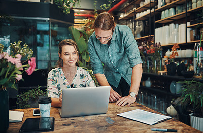 Buy stock photo Cropped shot of two young businesspeople sitting and working on a laptop during a discussion in their floristry