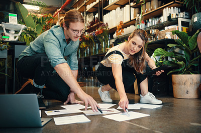 Buy stock photo Full length shot of two young businesspeople crouching in their floristry and discussing paperwork on the floor