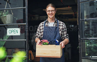 Buy stock photo Cropped portrait of a handsome young business owner holding a crate of flowers at the entrance of his floristry