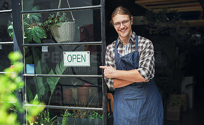 Buy stock photo Cropped portrait of a handsome young business owner pointing at the open sign at the entrance of his floristry