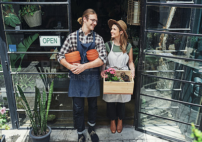 Buy stock photo Full length shot of two young business owners standing at the entrance of their floristry together and holding potting supplies