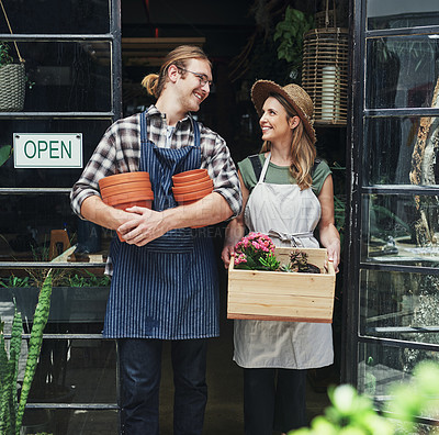 Buy stock photo Cropped shot of two young business owners standing at the entrance of their floristry together and holding potting supplies