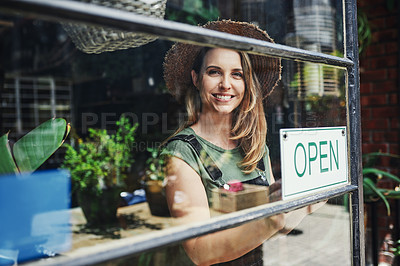Buy stock photo Cropped portrait of an attractive young business owner standing alone at the entrance of her flower shop